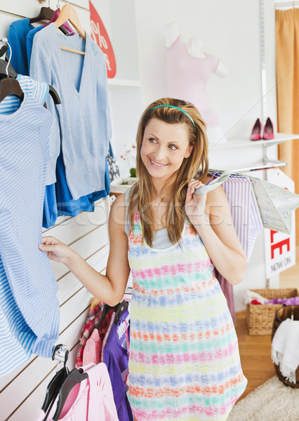 Stock photo: Cute young woman choosing clothes in a shop holding shopping bags