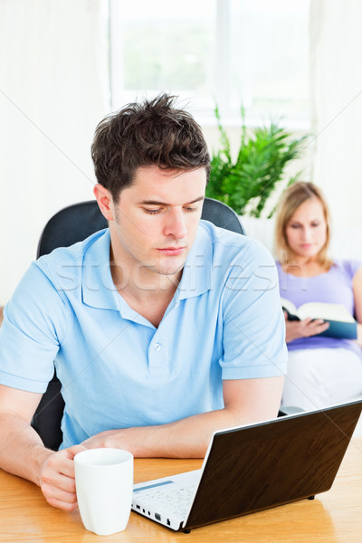 concentrated man working on his laptop with his girlfriend reading in the background at home Stock photo © wavebreak_media