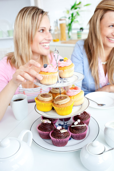 Stock photo: Portrait of two smiling female friends eating pastries in the kitchen at home