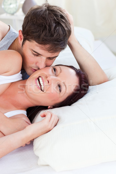 Cheerful caucasian couple lying on bed at home Stock photo © wavebreak_media