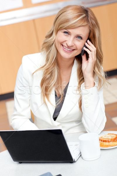 Radiant businesswoman with laptop, coffee and food talking on phone at work Stock photo © wavebreak_media