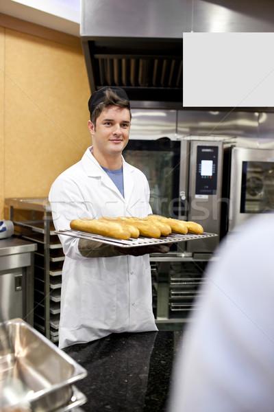 Jonge bakker baguettes permanente keuken Stockfoto © wavebreak_media