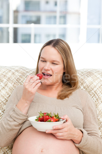 Hungry pregnant woman eating strawberries sitting in the living-room at home Stock photo © wavebreak_media