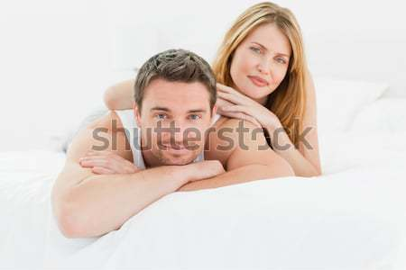Lovely pairs lying down together in their bed at home Stock photo © wavebreak_media