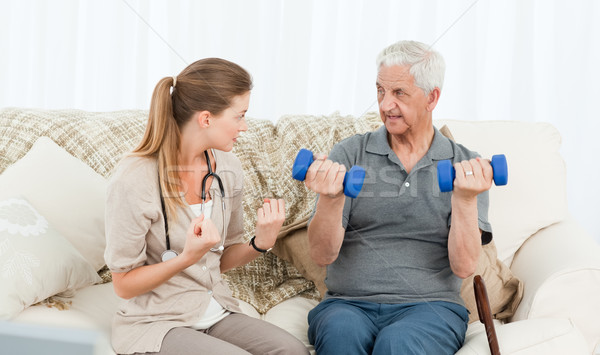Lovely nurse helping her patient to do exercises at home Stock photo © wavebreak_media