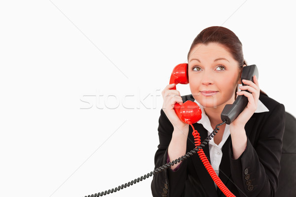 Cute secretary answering two phone calls at the same time against a white background Stock photo © wavebreak_media