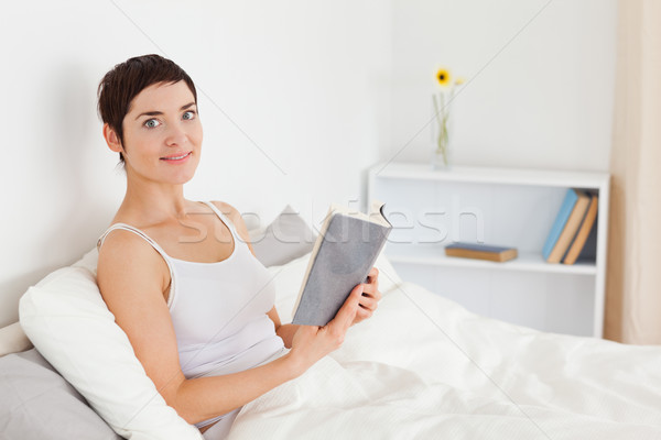 Stock photo: Young woman holding a book while looking at the camera