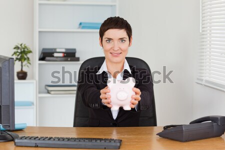 Cute office worker breaking a piggybank with a hammer in her office Stock photo © wavebreak_media