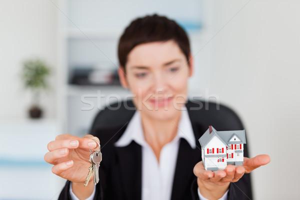 Mosolygó nő mutat miniatűr ház kulcs kamera Stock fotó © wavebreak_media