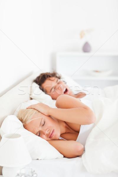 Portrait of an annoyed woman awaken by her boyfriend's snoring in their bedroom Stock photo © wavebreak_media