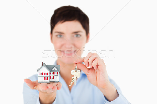 Close up of a woman showing keys and a miniature house against a white background Stock photo © wavebreak_media