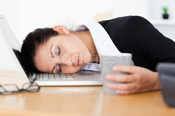 An exhausted businesswoman is sleeping with her head on laptop Stock photo © wavebreak_media