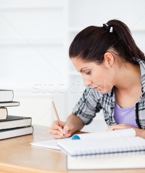 A young student is writing in her exercise book Stock photo © wavebreak_media