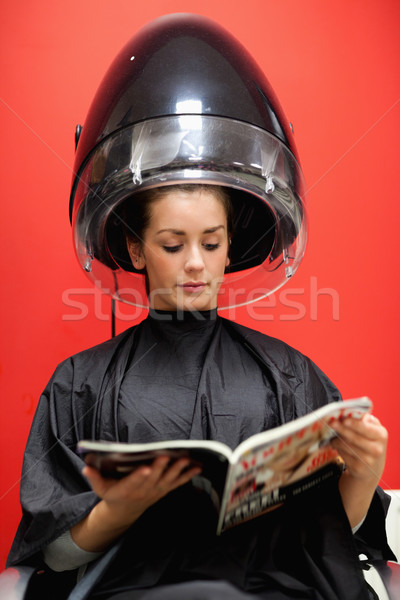 Stock photo: Portrait of a student under a hairdressing machine while reading a magazine