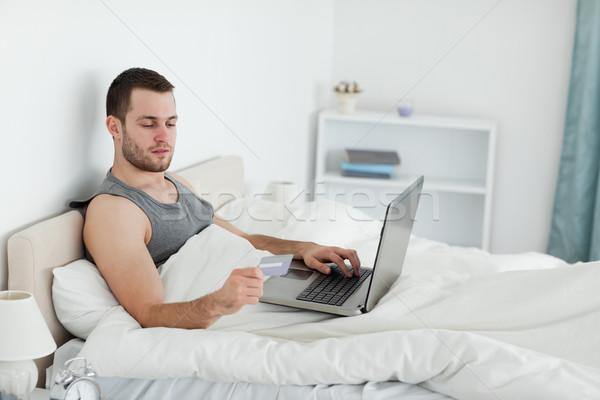 Young man purchasing online in his bedroom Stock photo © wavebreak_media