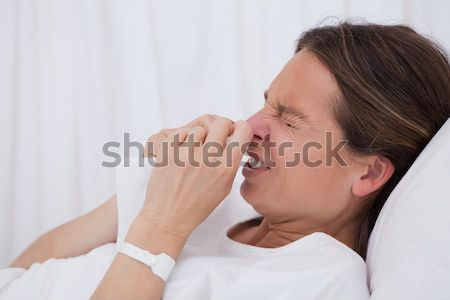 Side view of sneezing woman laying in bed Stock photo © wavebreak_media