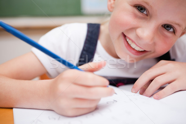 Close up of a smiling schoolgirl writing something in a classroom Stock photo © wavebreak_media