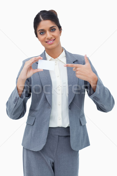 Saleswoman pointing at blank business card against a white background Stock photo © wavebreak_media