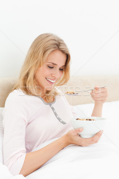 A woman sitting in bed with a bowl of cereal in her and and a spoon of cereal near her mouth as she  Stock photo © wavebreak_media