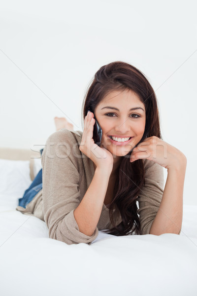 A close up shot of a woman smiling and looking in front of her as she makes a phonecall on the bed. Stock photo © wavebreak_media