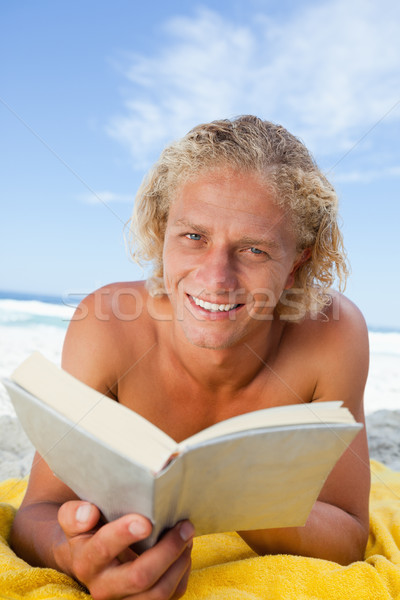 Smiling blonde man reading a book while lying on the beach Stock photo © wavebreak_media