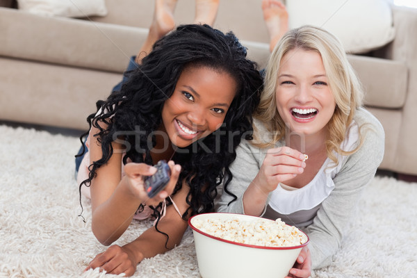 Two women lying on the ground with popcorn are smiling at the camera nd holding a TV remote Stock photo © wavebreak_media