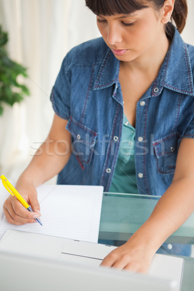 Unsmiling student doing her homework with her laptop Stock photo © wavebreak_media
