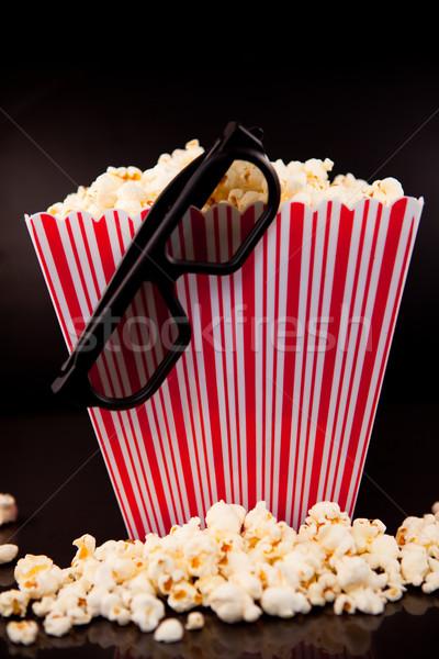 3D glasses hanging on a box full of popcorn against a black background Stock photo © wavebreak_media
