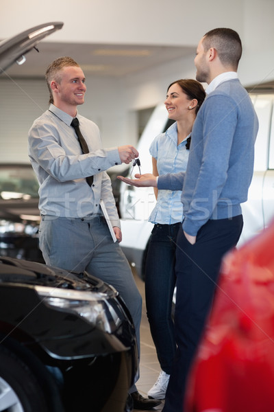 Stock photo: Salesman giving car keys to a couple in front of an open car engine