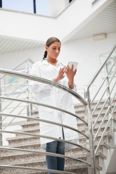Stock photo: Doctor touching a tablet computer in hospital stairs