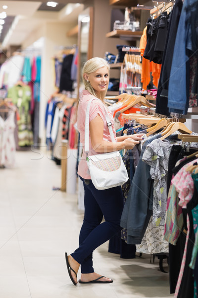 Woman standing in a shop looking at the camera smiling searching for clothes Stock photo © wavebreak_media