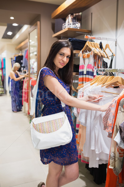 Smiling woman looking through clothes in shopping mall Stock photo © wavebreak_media