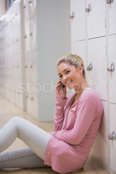 Woman sitting on the floor against lockers at the hallway while phoning and smiling  Stock photo © wavebreak_media