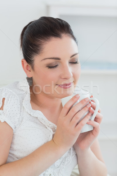 Young woman sitting on the couch in a living room and smelling the cup of coffee Stock photo © wavebreak_media