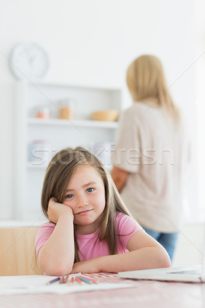 Stock photo: Little girl with paper and colouring pencils leaning on kitchen table with mother standing behind