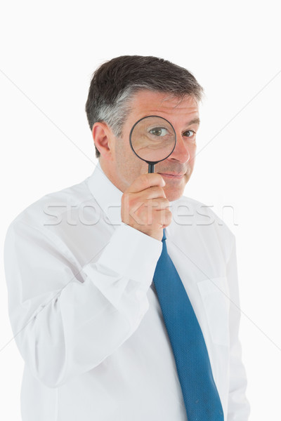 Inquisitive businessman looking through magnifying glass Stock photo © wavebreak_media