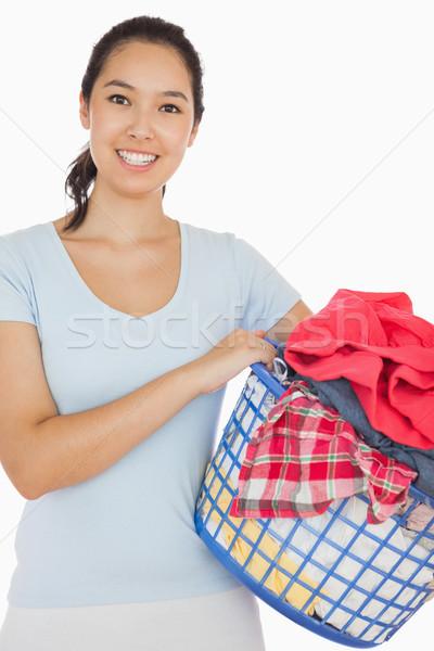 Smiling woman holding a basket full of laundry on a white background Stock photo © wavebreak_media