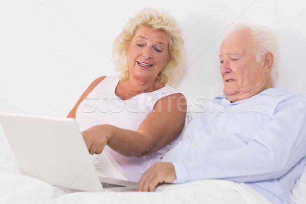 Yaşlı çift dizüstü bilgisayar kullanıyorsanız yatak bilgisayar kadın ev Stok fotoğraf © wavebreak_media