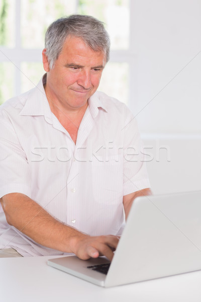 Old man concentrating in front of his laptop  Stock photo © wavebreak_media