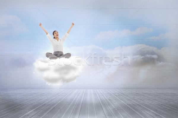 Composite image of cheering businesswoman sitting cross legged Stock photo © wavebreak_media