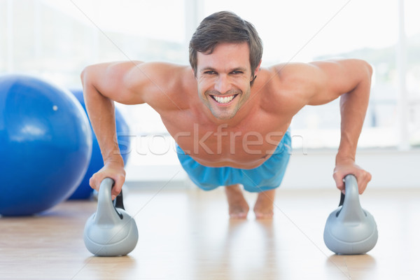 Portrait of a smiling young man doing push ups Stock photo © wavebreak_media