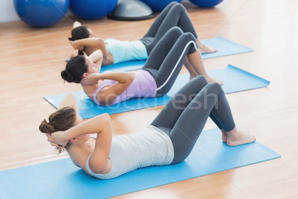 Determined women doing sit ups at fitness studio Stock photo © wavebreak_media