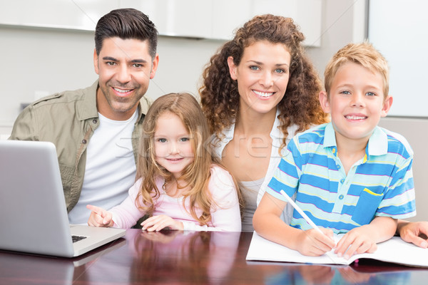 Happy parents colouring and using laptop with their young childr Stock photo © wavebreak_media