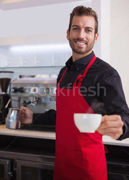 Happy young barista holding jug and cup of coffee Stock photo © wavebreak_media