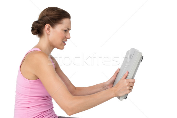 Annoyed young woman with weight scale Stock photo © wavebreak_media
