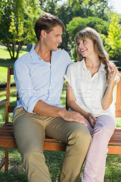 Cute couple sitting on park bench together chatting Stock photo © wavebreak_media