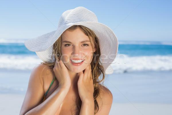 Beautiful girl in white straw hat smiling at camera on beach Stock photo © wavebreak_media