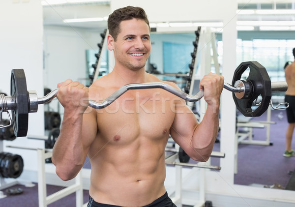 Shirtless smiling bodybuilder lifting heavy barbell weight  Stock photo © wavebreak_media