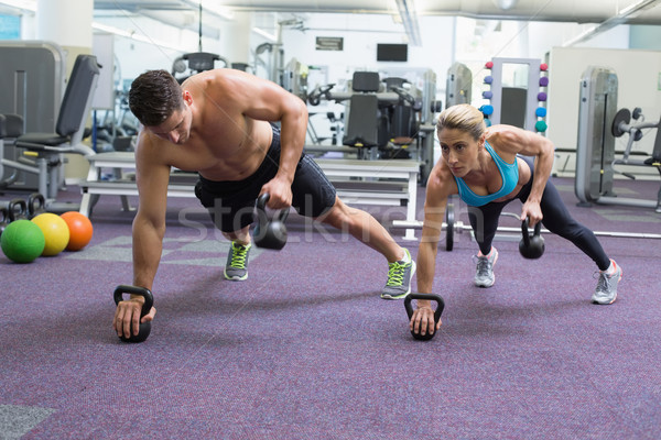 Bodybuilding man and woman lifting kettlebells in plank position Stock photo © wavebreak_media