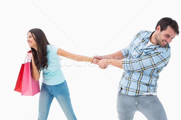 Attractive young man pulling his shopaholic girlfriend Stock photo © wavebreak_media